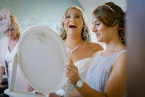 The bride laughs with her bridesmaides