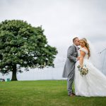 Bride and groom by te tree at Heaton House Farm