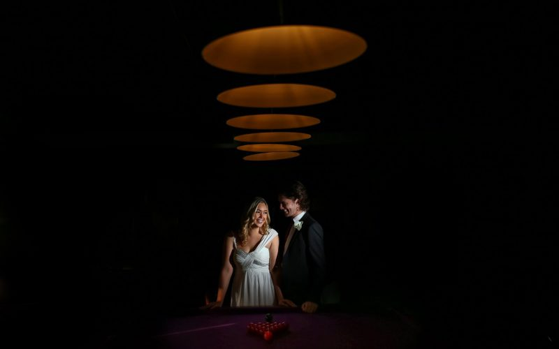 Bride and groom laughing beneath circular light shades