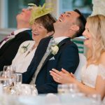 The groom laughs at the top table
