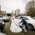 The father of the bride helps his daughter out of the car