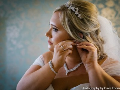 The bride puts in her earrings at Heaton House Farm