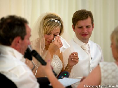 The bride wipes a tear as her dad makes a speech.