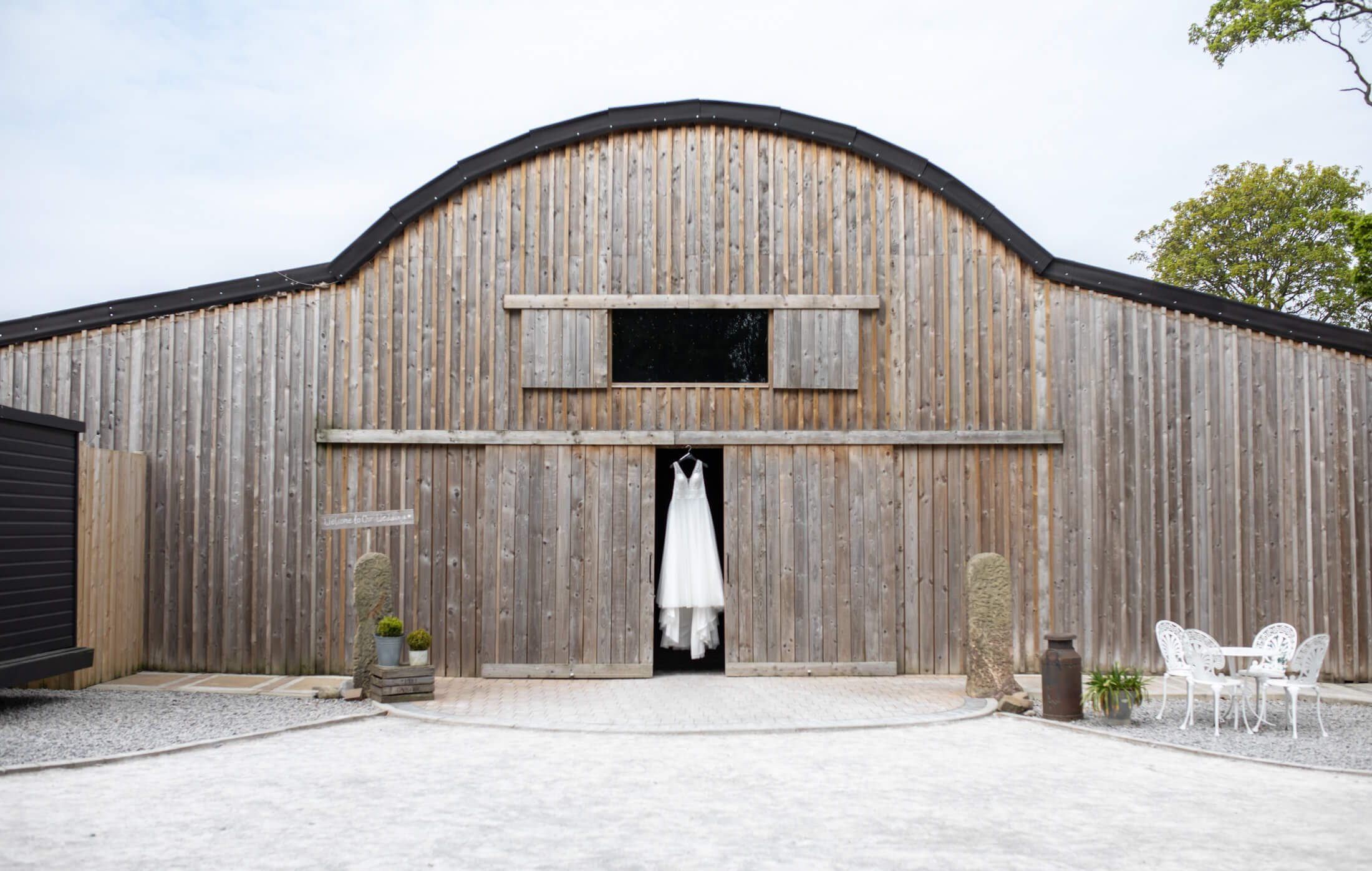 Alcumlow Wedding Barn with a dress hung in the doorway of the barn