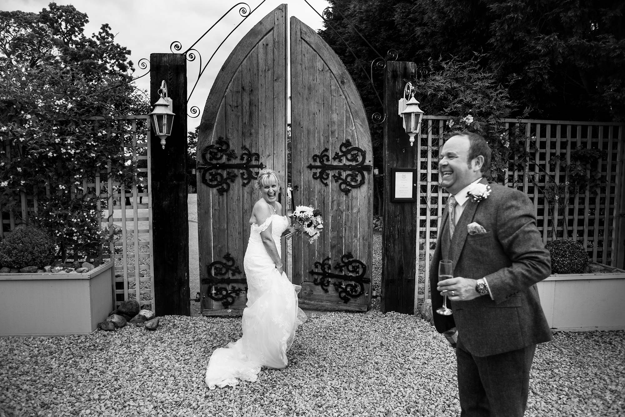 Black and white image of the bide and groom laughing as they enter the gates at Alcumlow Farm