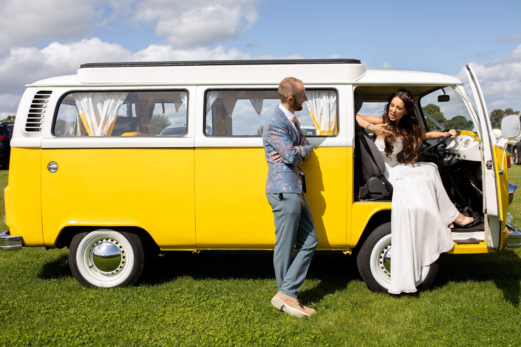 A bride talks to her husband as she sits behind the wheel of a yellow VW camper van