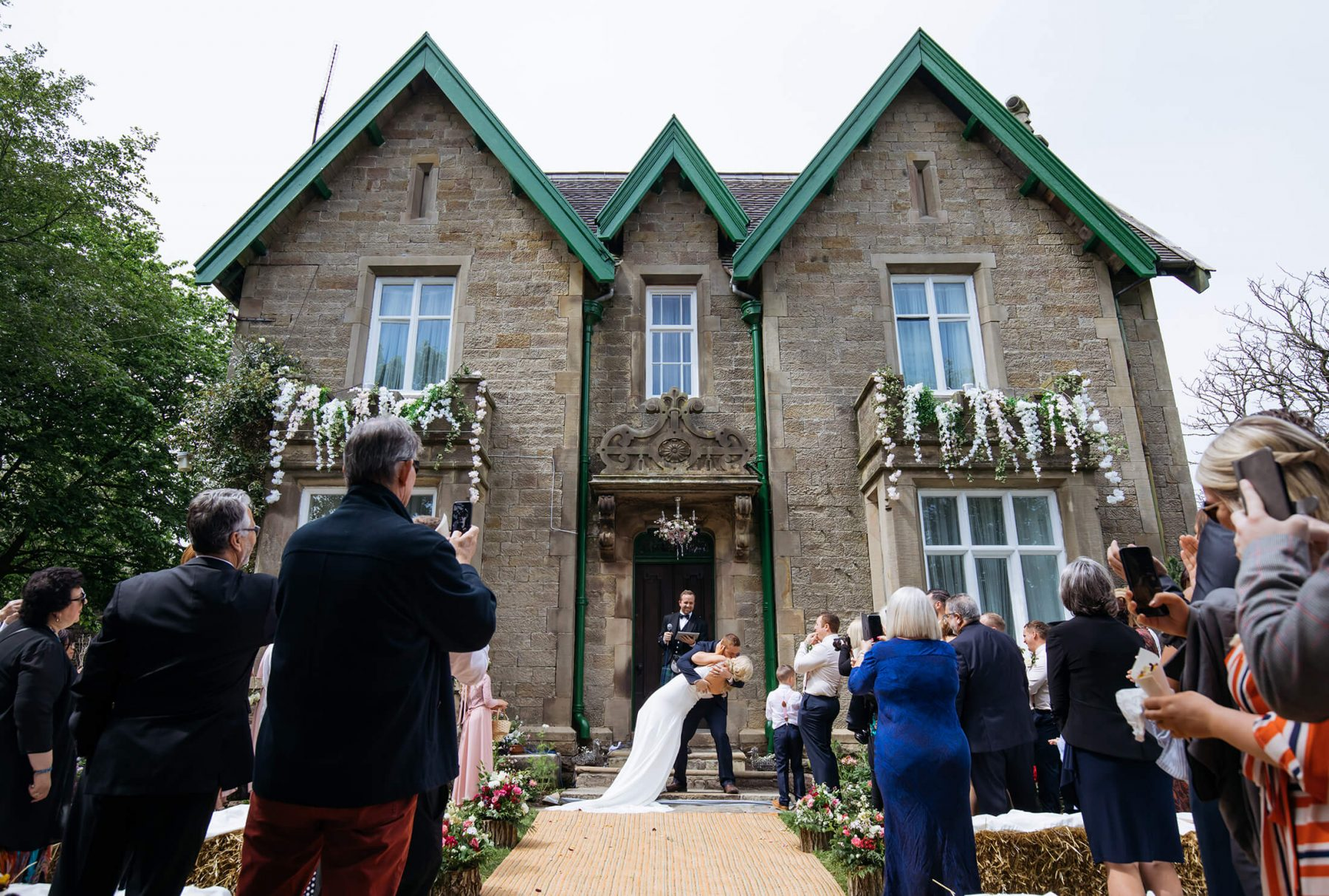 The bride and groom kiss outside a county house following their wedding