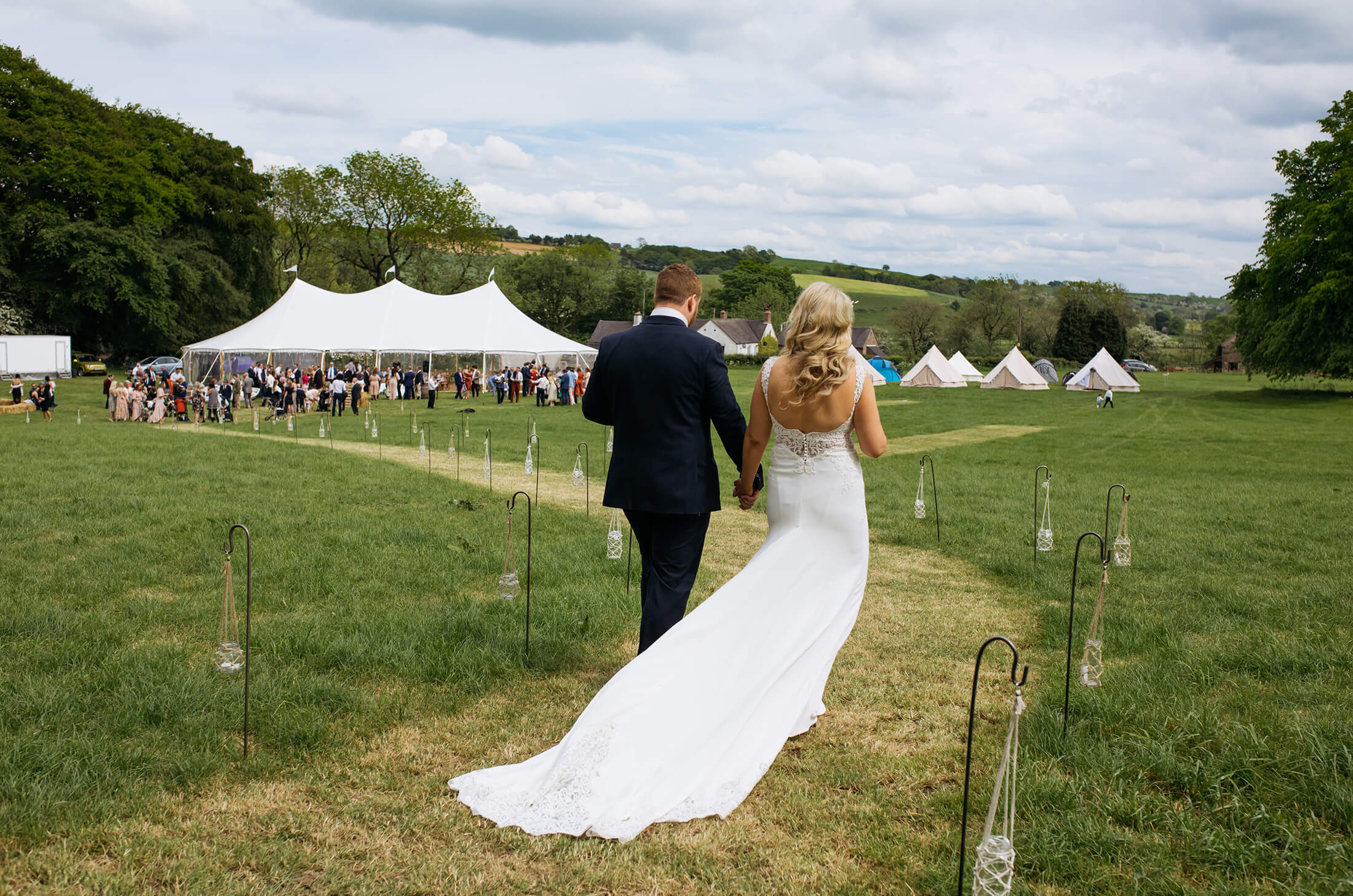 The bride and groom make their way to the marquee for their wedding celebrations.