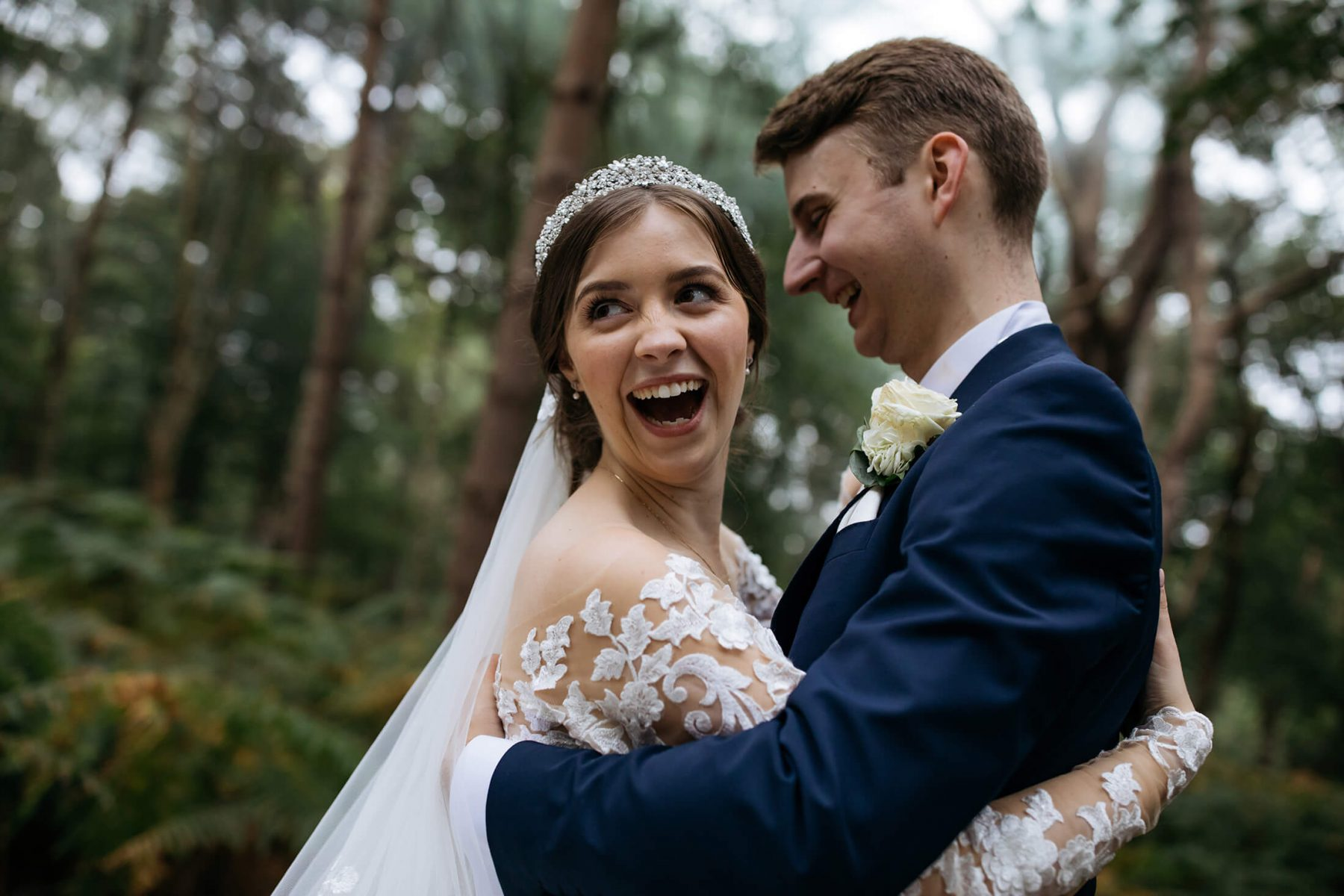 A bride and groom smile for a wedding portrait