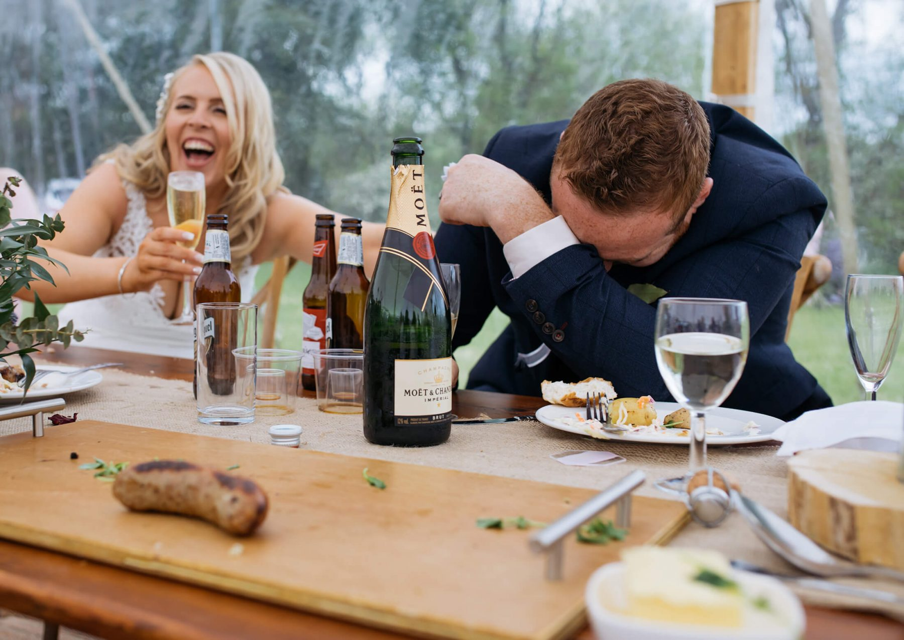 A groom slumps on a table as the bride laughs during the speeches at a summer wedding in Cheshire