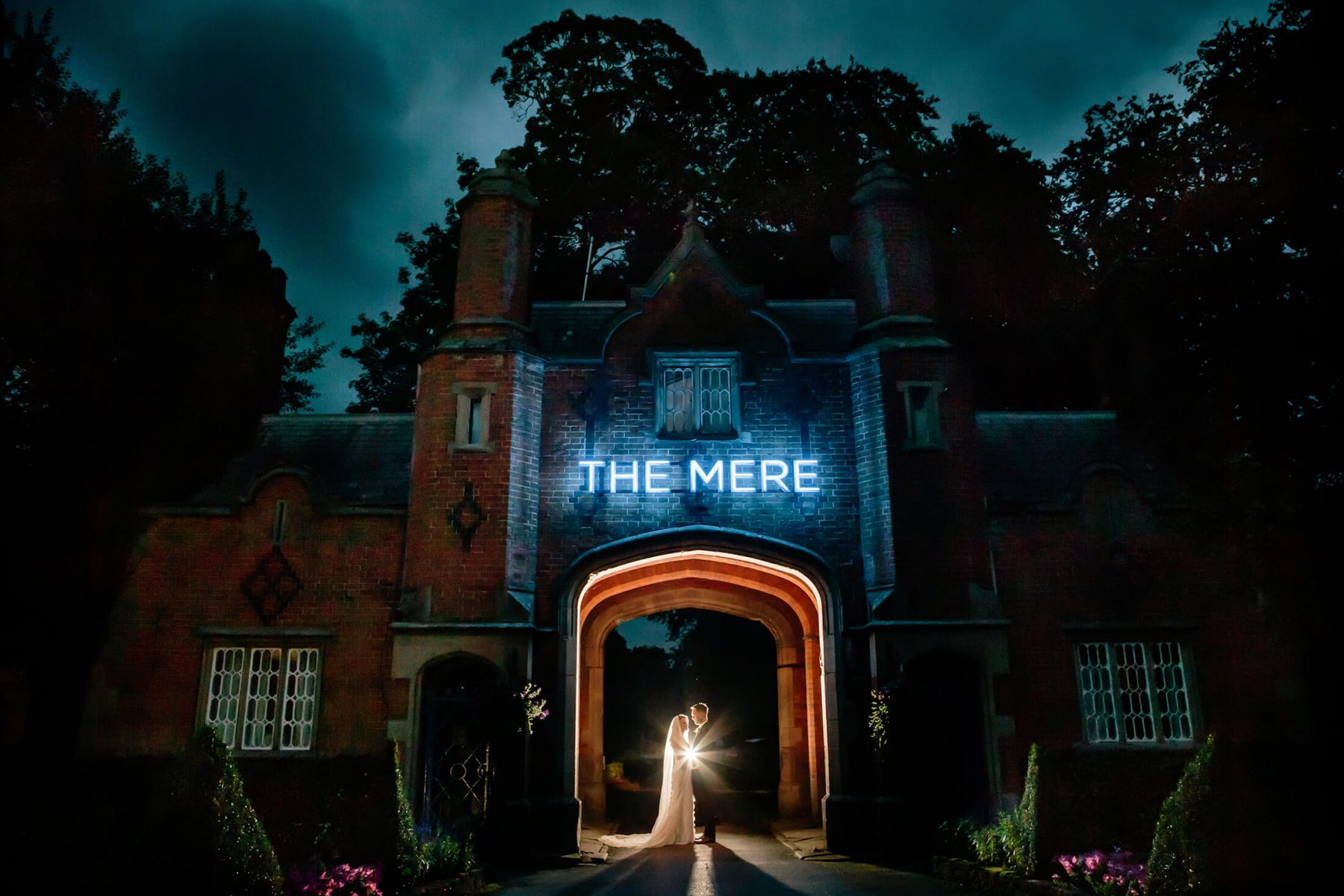 A night time portrait of the bride and groom under the arch at the Mere Golf Resort & Spa in Cheshire. Mere Resort Wedding Photographer