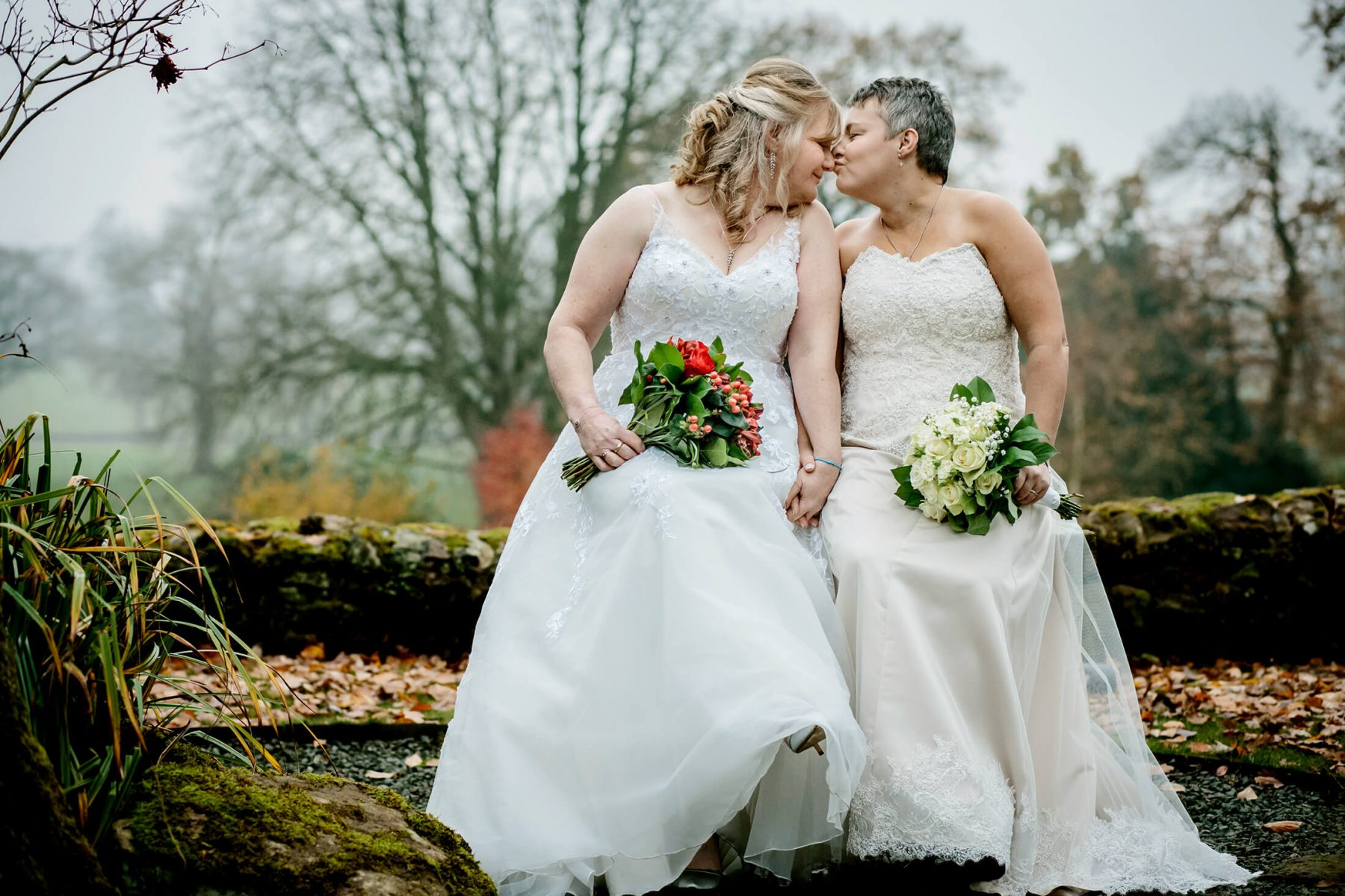Two brides share a kiss after their wedding at The Upperhouse Hotel in Staffordshire. Same sex wedding photographer