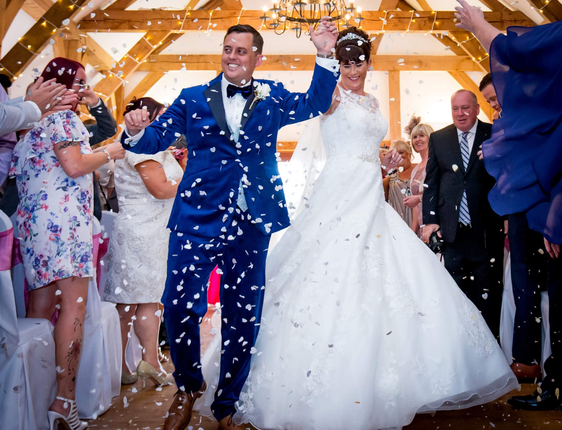 The bride and groom dance down the aisle following their wedding at Sandhole Oak Barn in Cheshire. Sandhole Oak Barn Wedding Photographer