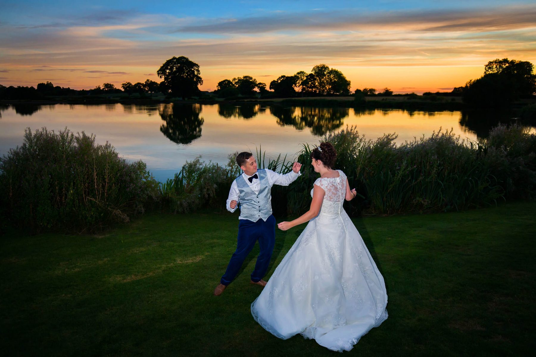 The bride and groom dance in front of the lake and a sunset after their wedding at Sandhole Oak Barn in Cheshire. Sandhole Oak Barn Wedding Photographer