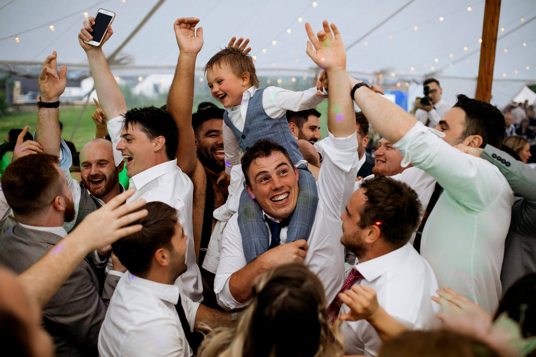 A young boy is lofted onto a mans shoulders on the dancefloor during the wedding party. Staffordshire Wedding Photographer