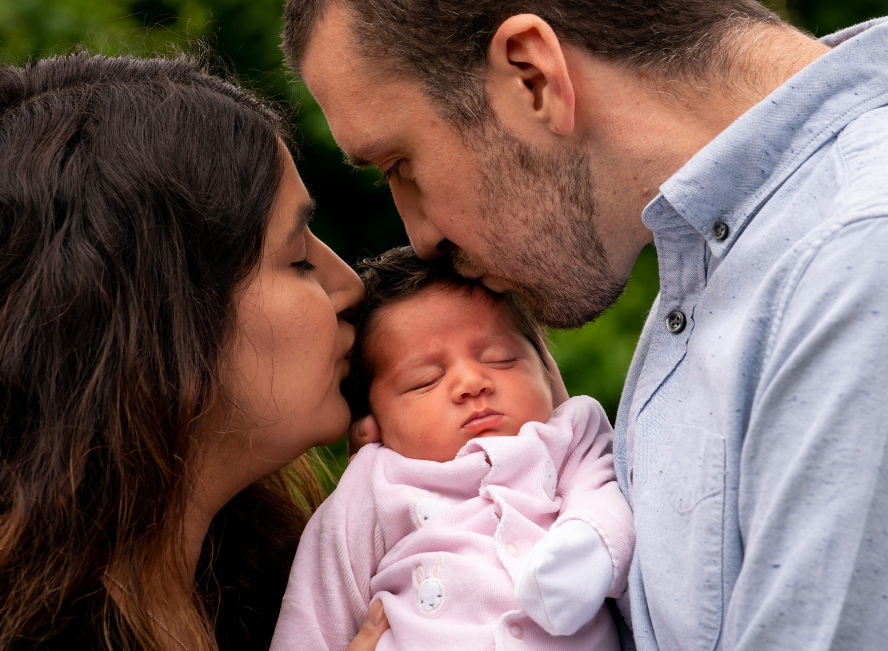 A parent and father kiss the head of their new born child in Stockport