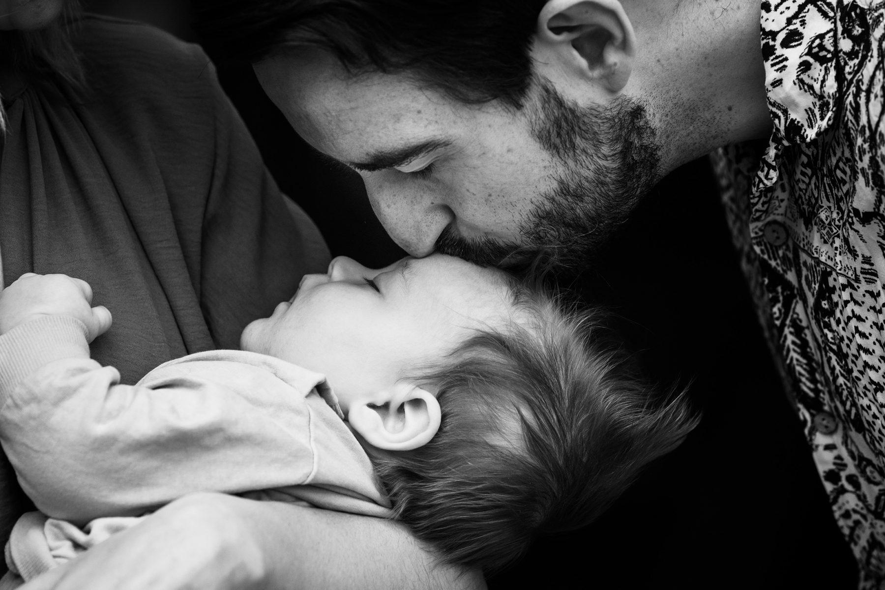 A father kisses his new born son's head