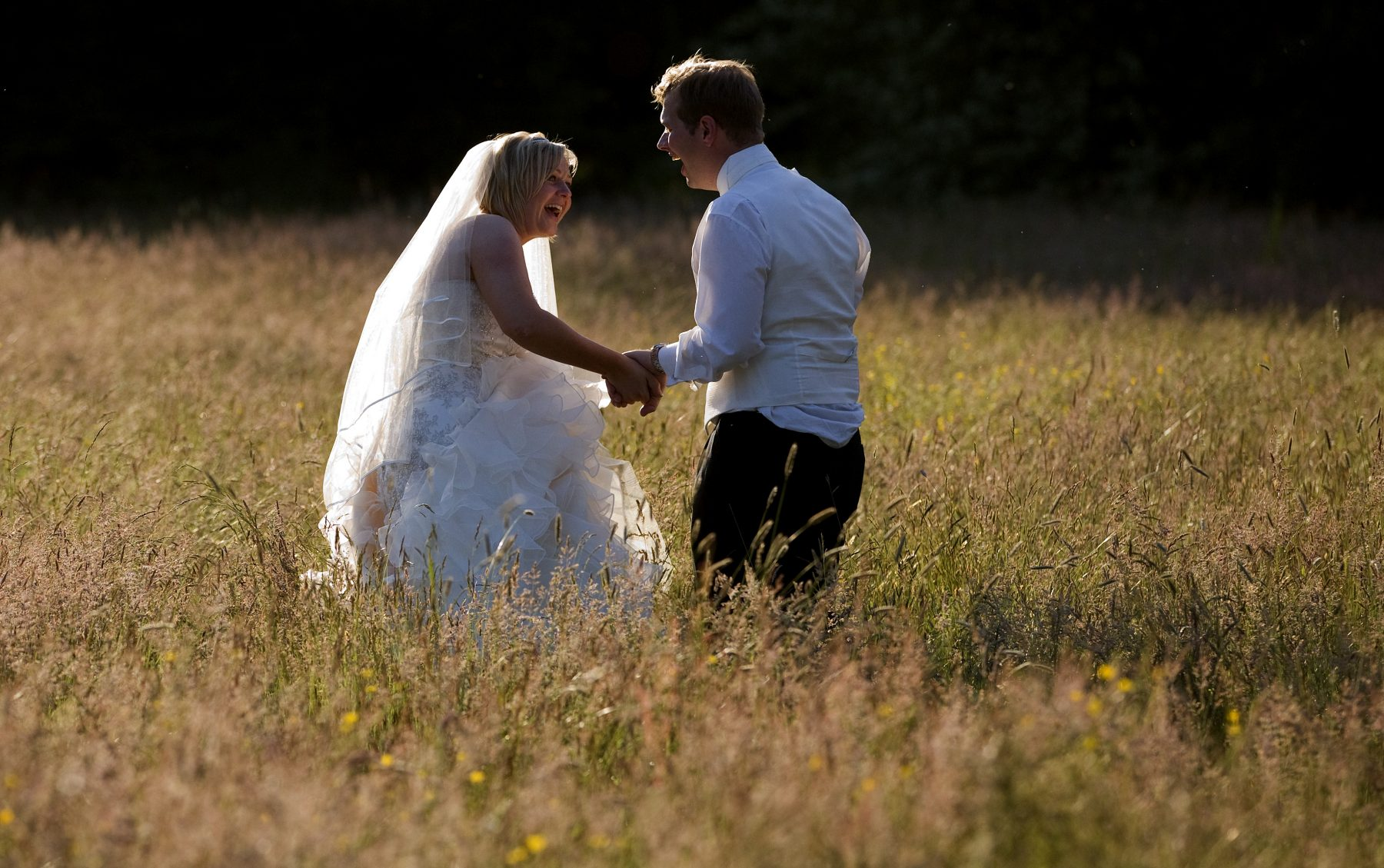 A bride and groom laugh during an evening sunset walk in the long grass after their wedding at Iscoyd Park in Shropshire.