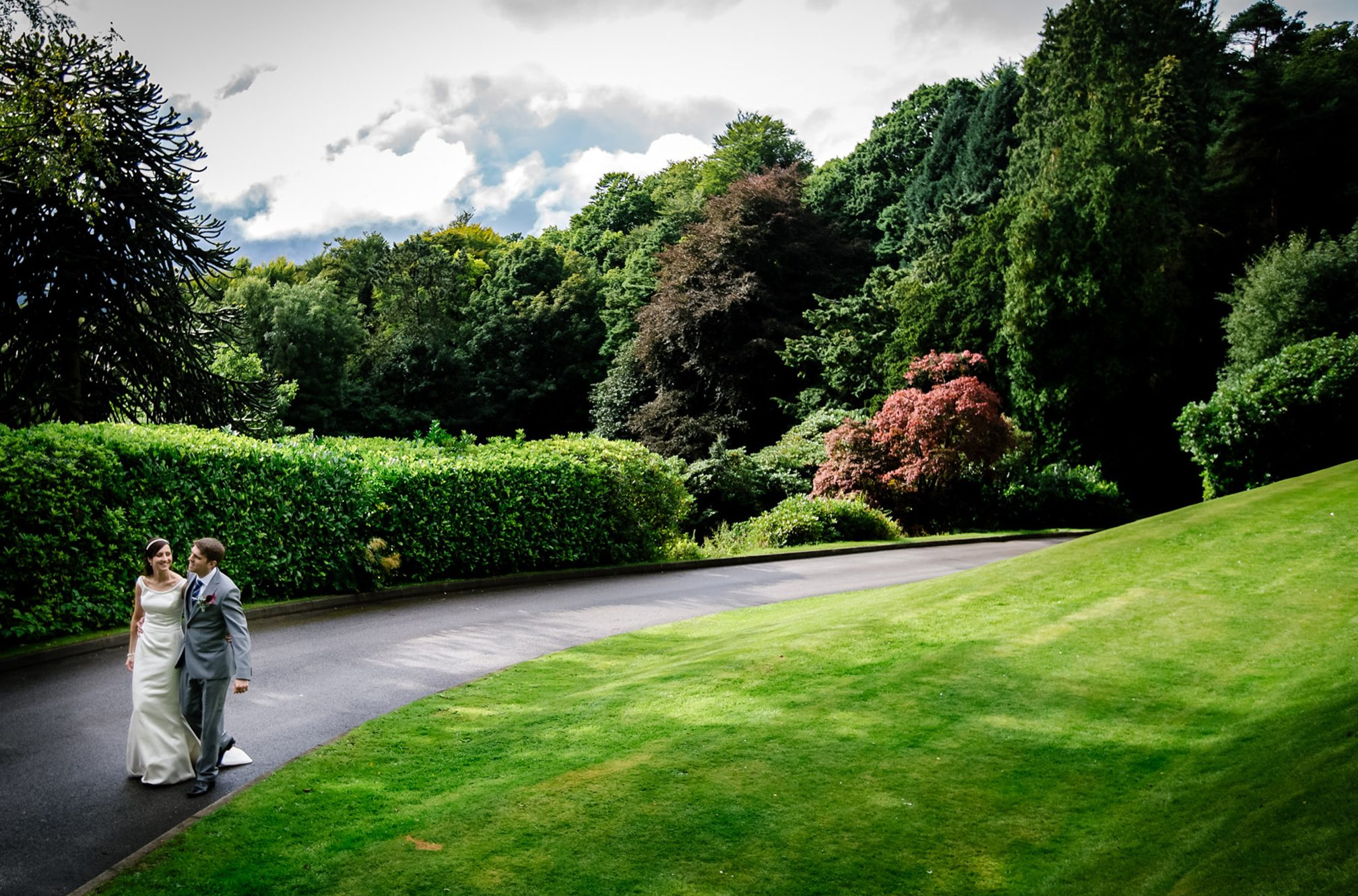 The bride and groom walk up the winding driveway at Merewood Country House Hotel.