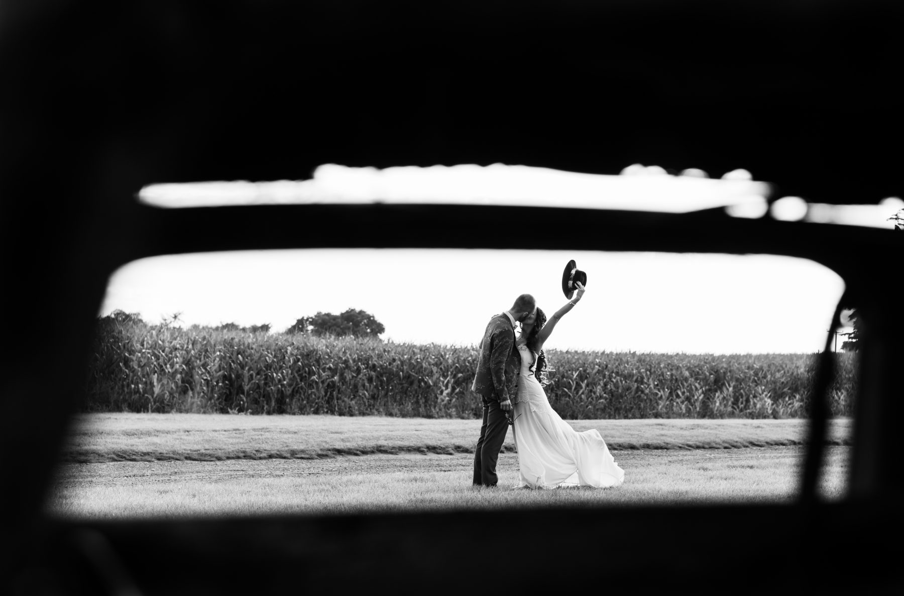 A bride and groom share a kiss at Alcumlow Wedding Barn