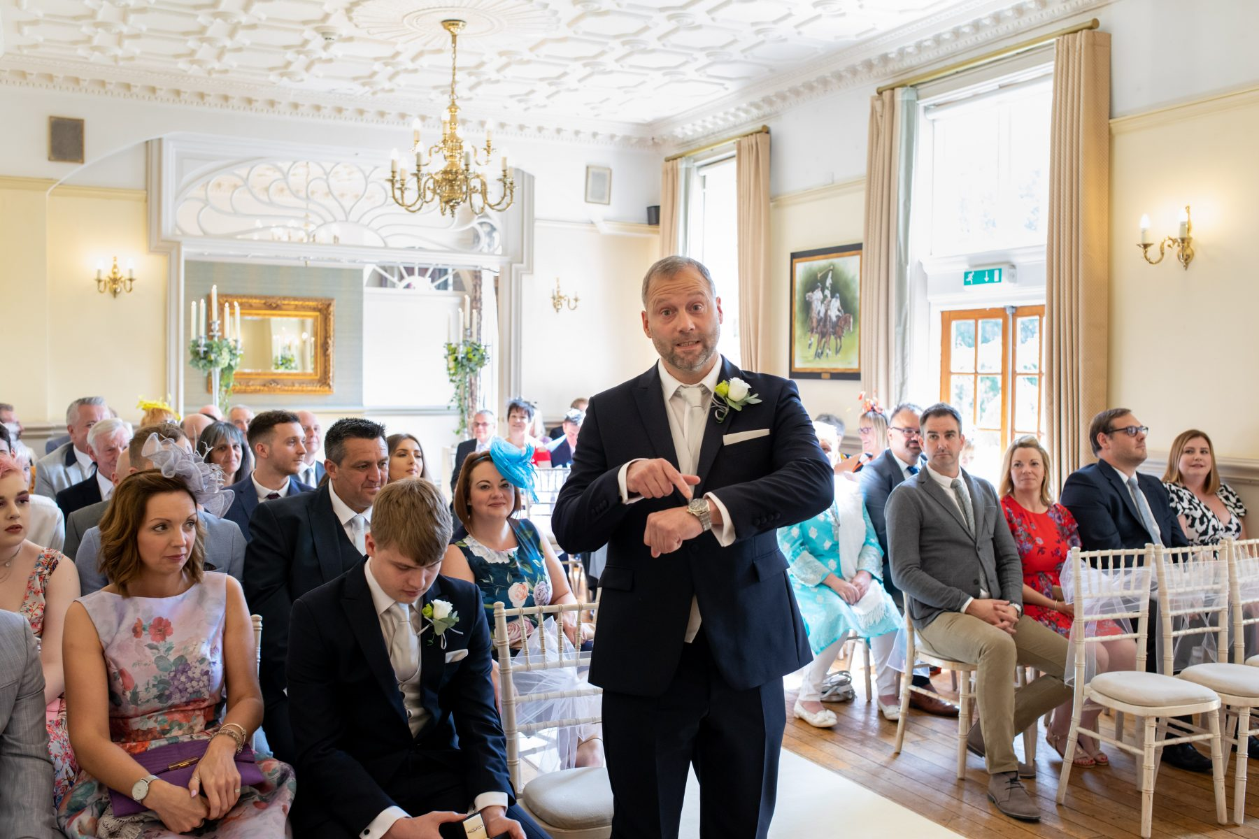 The groom points at this watch as the bride runs late ahead of a wedding at Nunsmere Hall in Cheshire