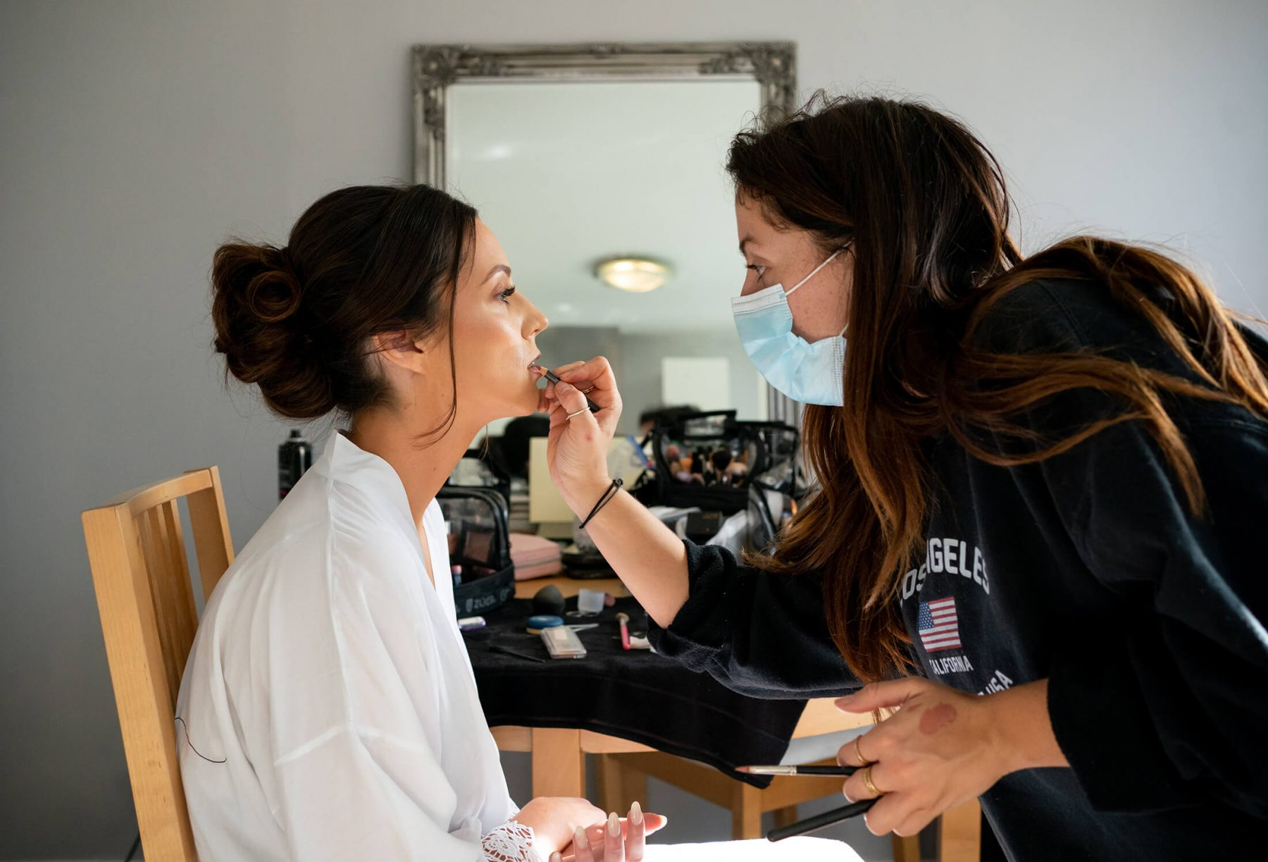 The bride getting ready at home while a makeup artist does her makeup