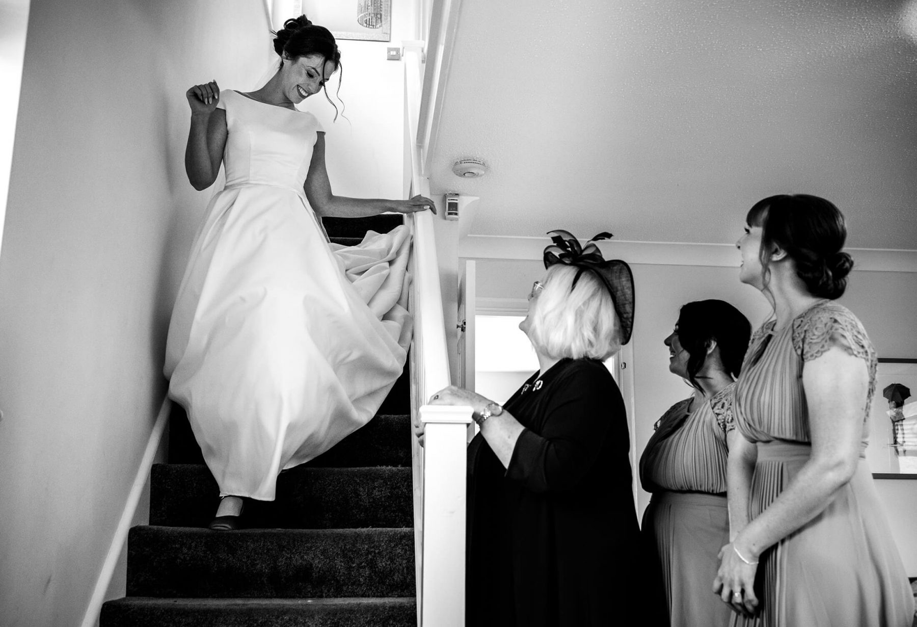 Bride coming down the stairs at her home in Manchester in her wedding dress