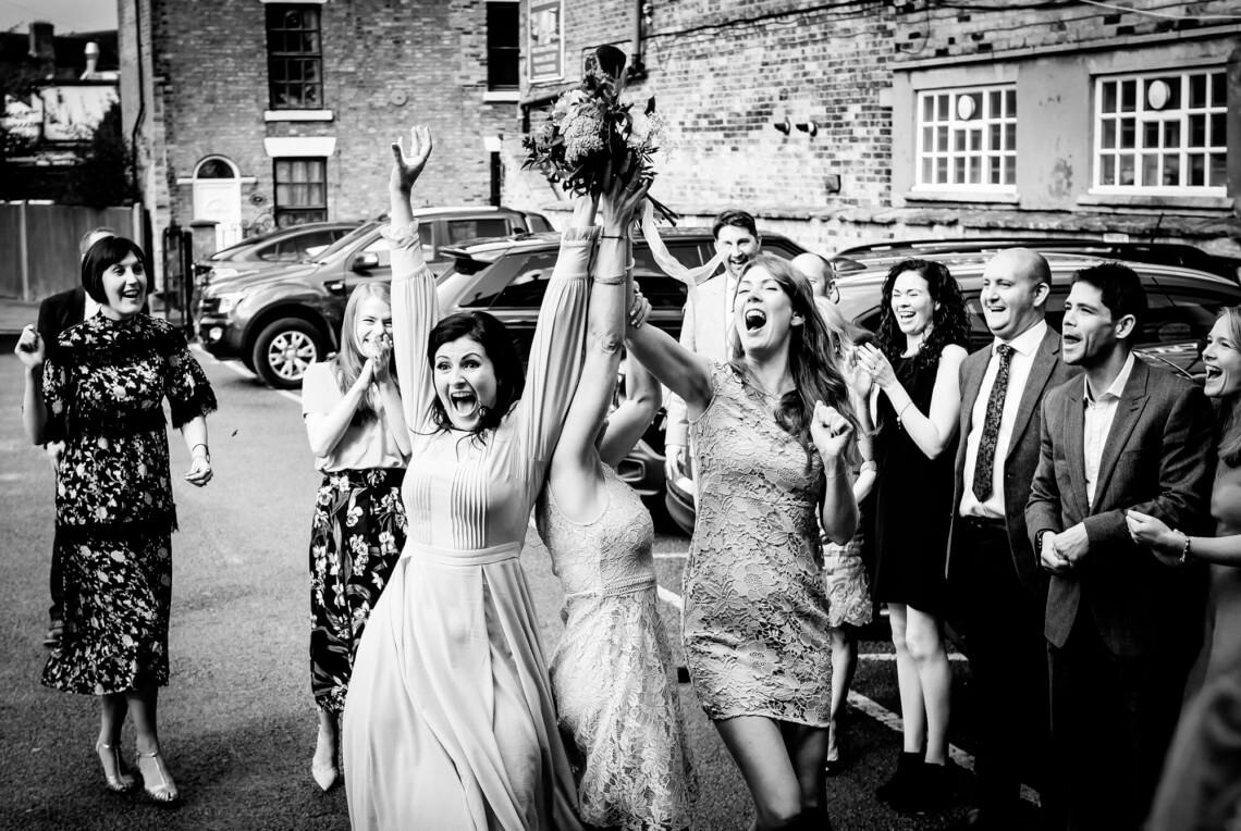 Natural wedding photographer capturing the bouquet toss