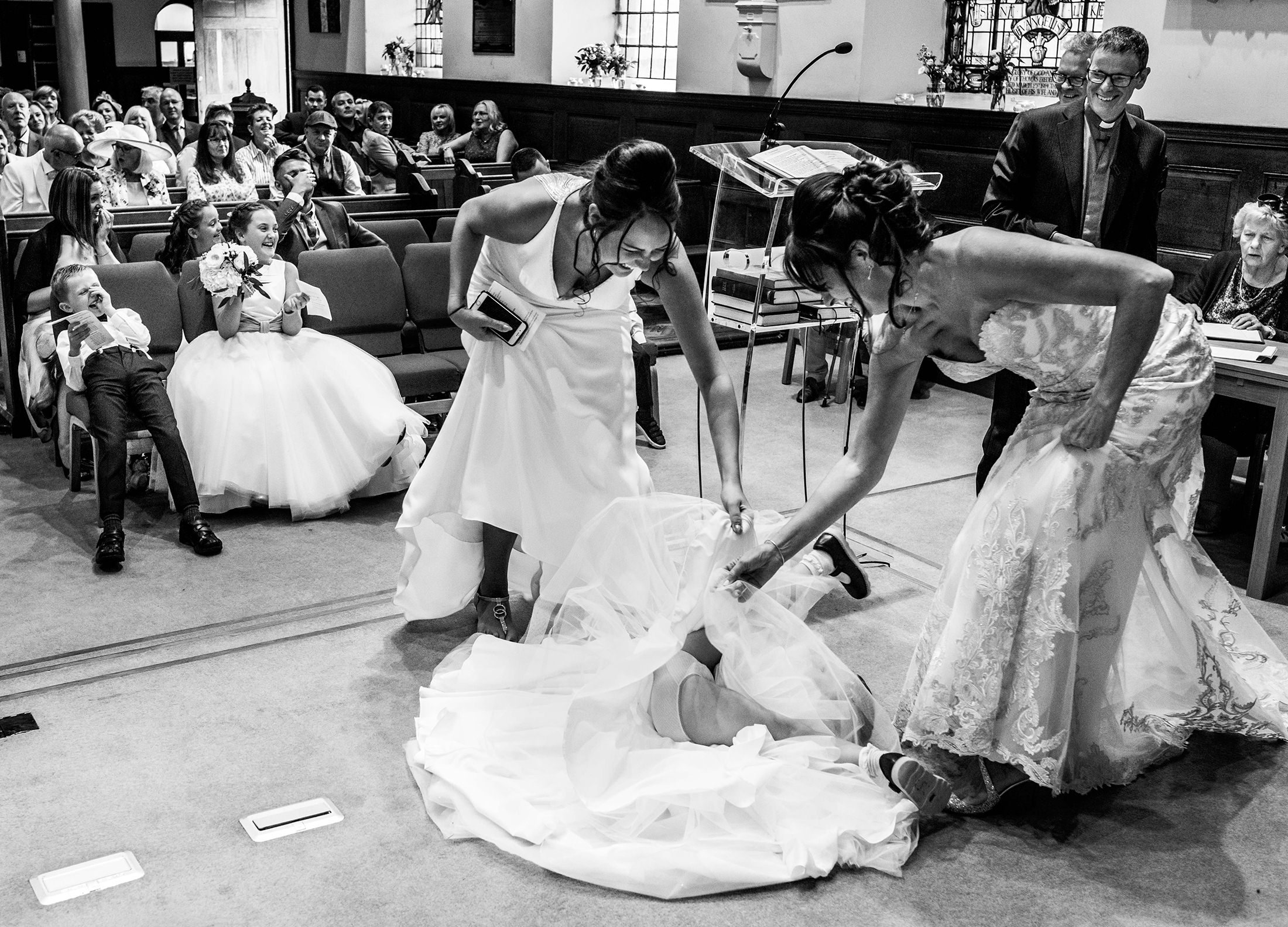 The bride and her daughter race to pull the dress of a flower girl during the wedding ceremony