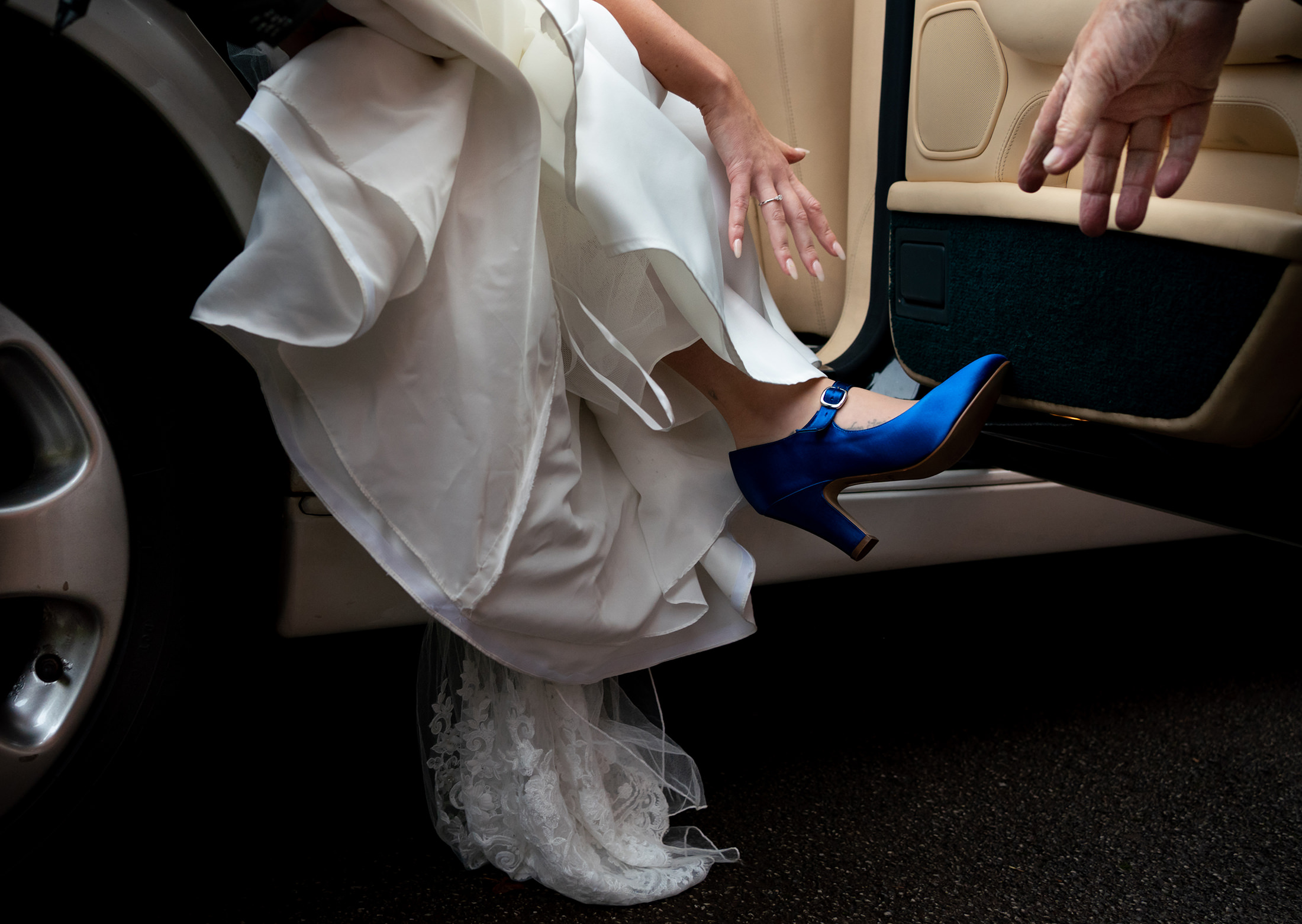 A bride steps out of the car wearing a blur shoe during this wedding in Altrincham in Cheshire