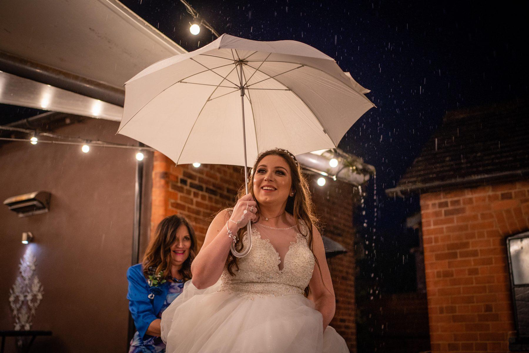 A bride walks with an umbrella