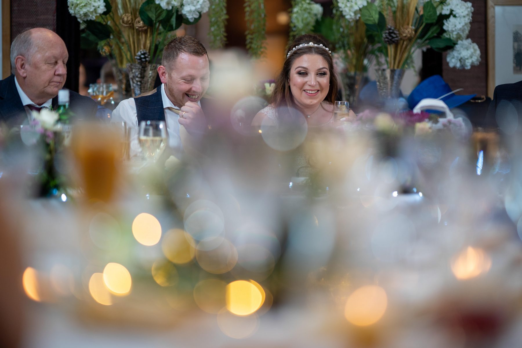 The bride and groom smile during the speeches