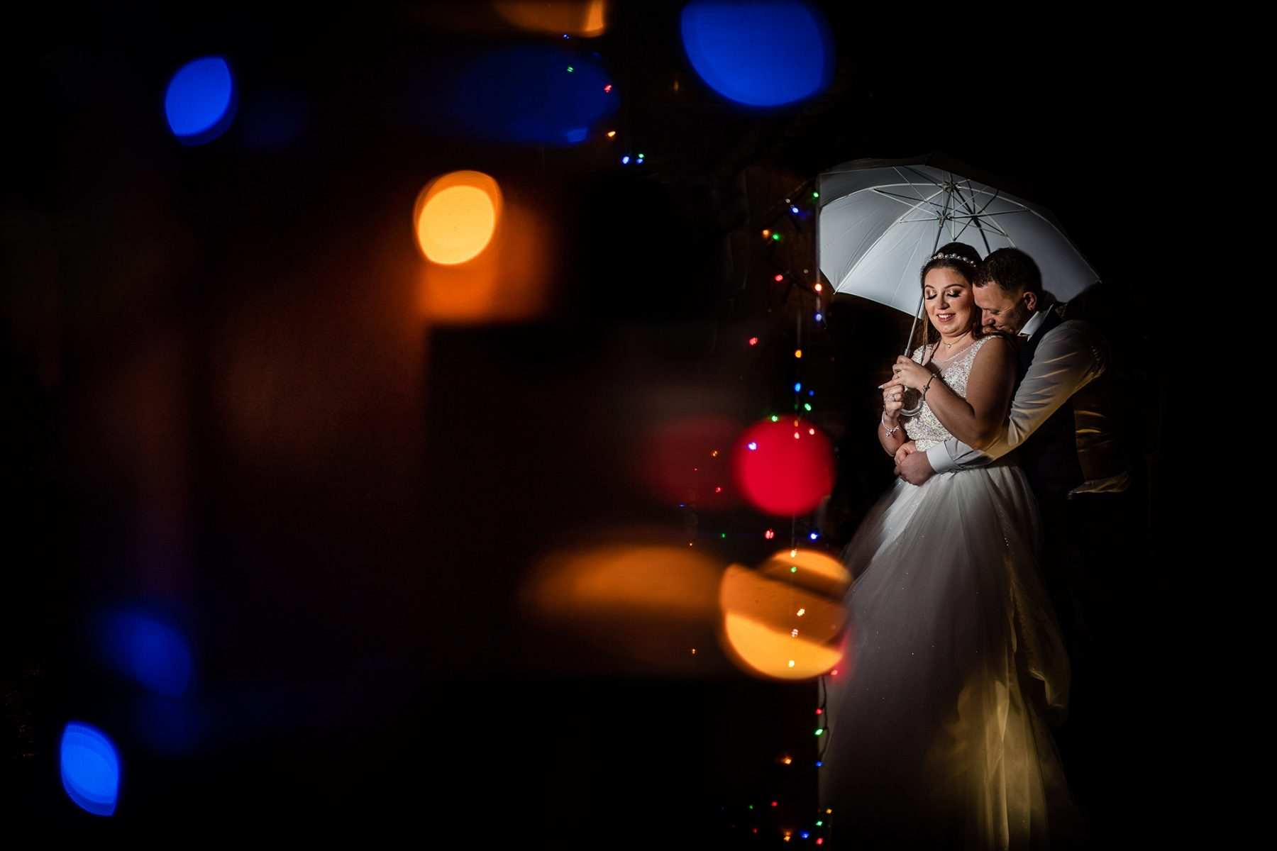 A creative off camera flash photograph of the bride and groom in the rain