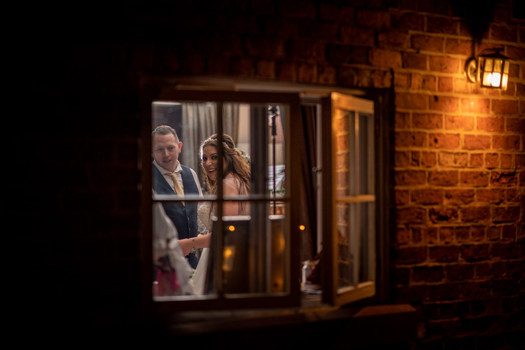 The married couple smile as they look through a window