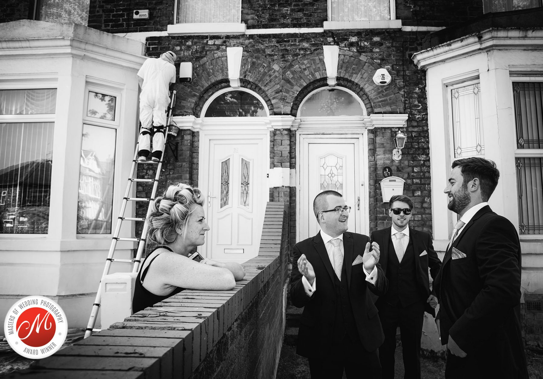 The groom talks to his groomsmen and a neighbour outside his house before his wedding in Liverpool, England.
