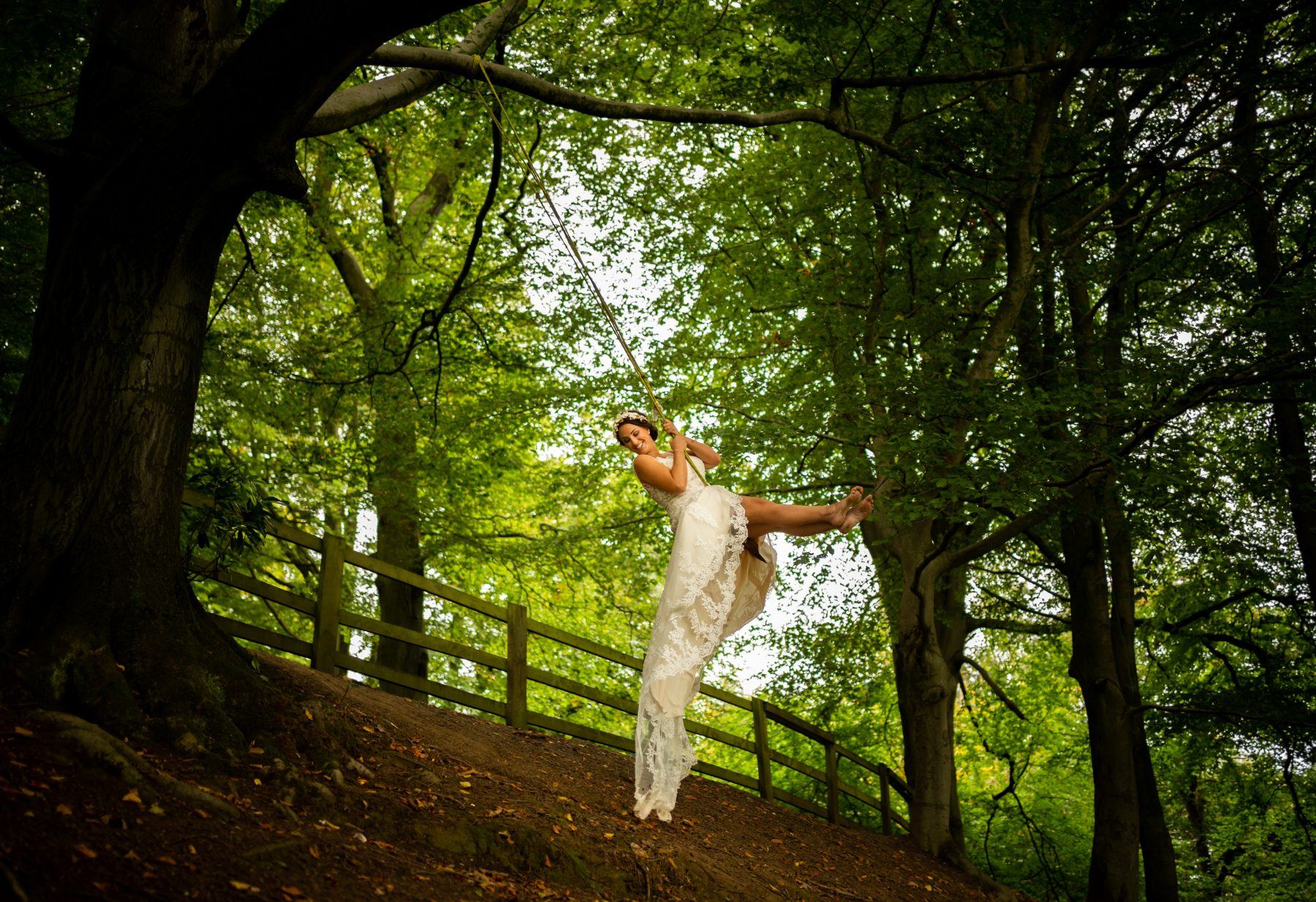 A bride swings on a rope swing during a photo shoot in Woodbank Park in Stockport