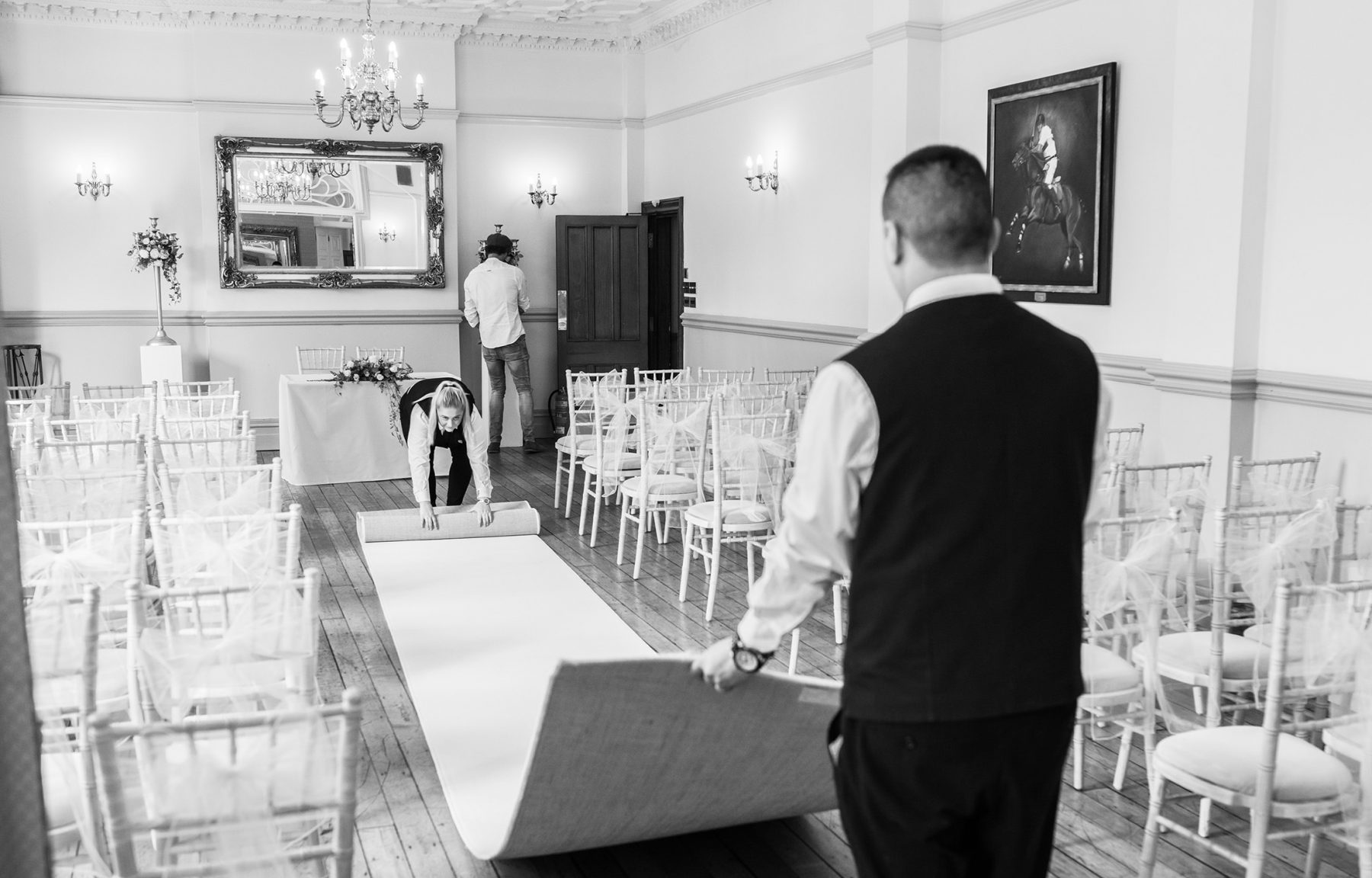 Staff prepare the wedding ceremony room before a Country House Wedding at Nunsmere Hall in Cheshire