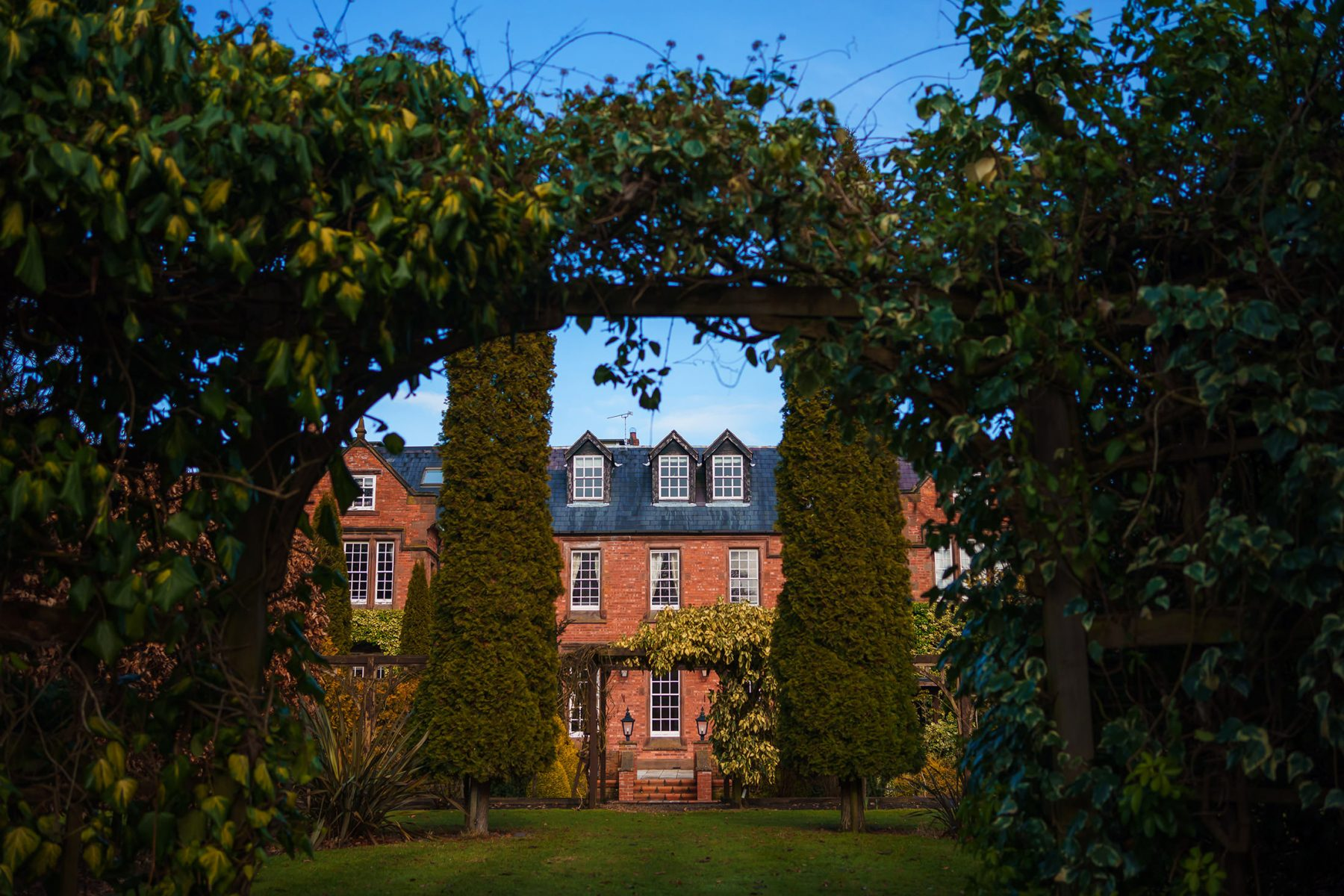 A photograph main building through an archway in the gardens at Nunsmere Hall in Cheshire - Country House weddings at Nunsmere Hall