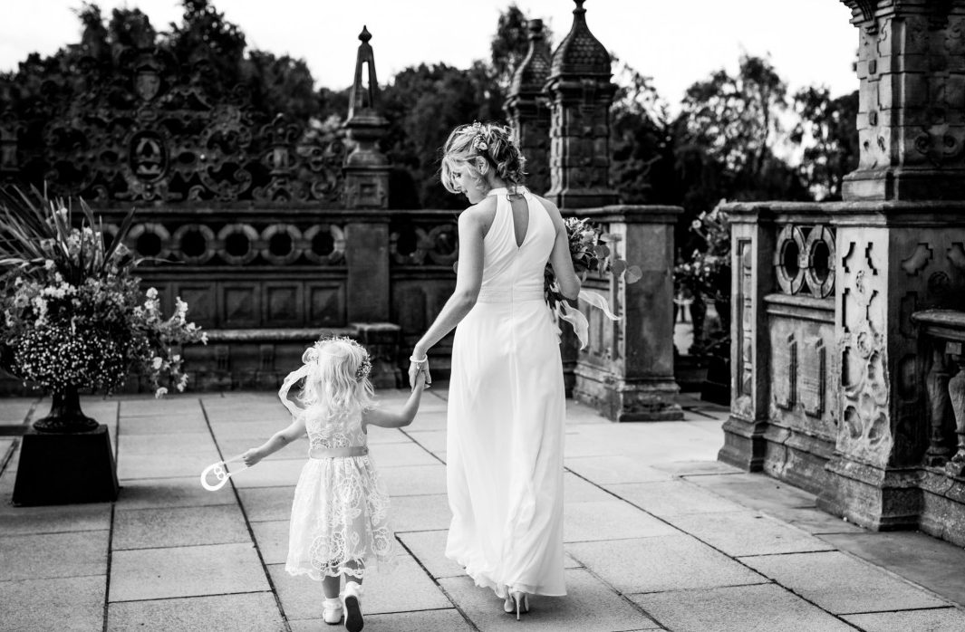 Relaxed wedding photography - A bride hand in hand with her young daughter at Crewe Hall