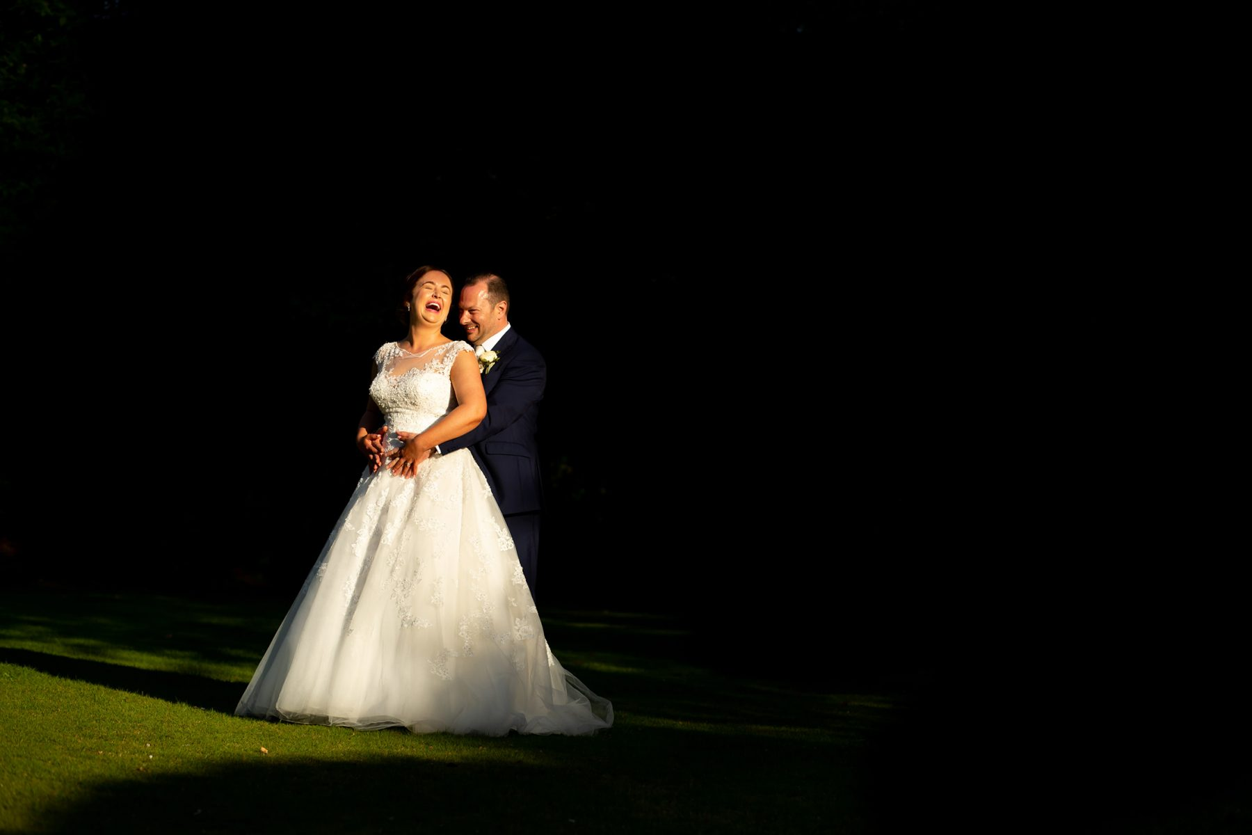 The bride and groom laugh in evening sunlight at the Mere Court Hotel, one of a number of Knutsford Wedding Venues