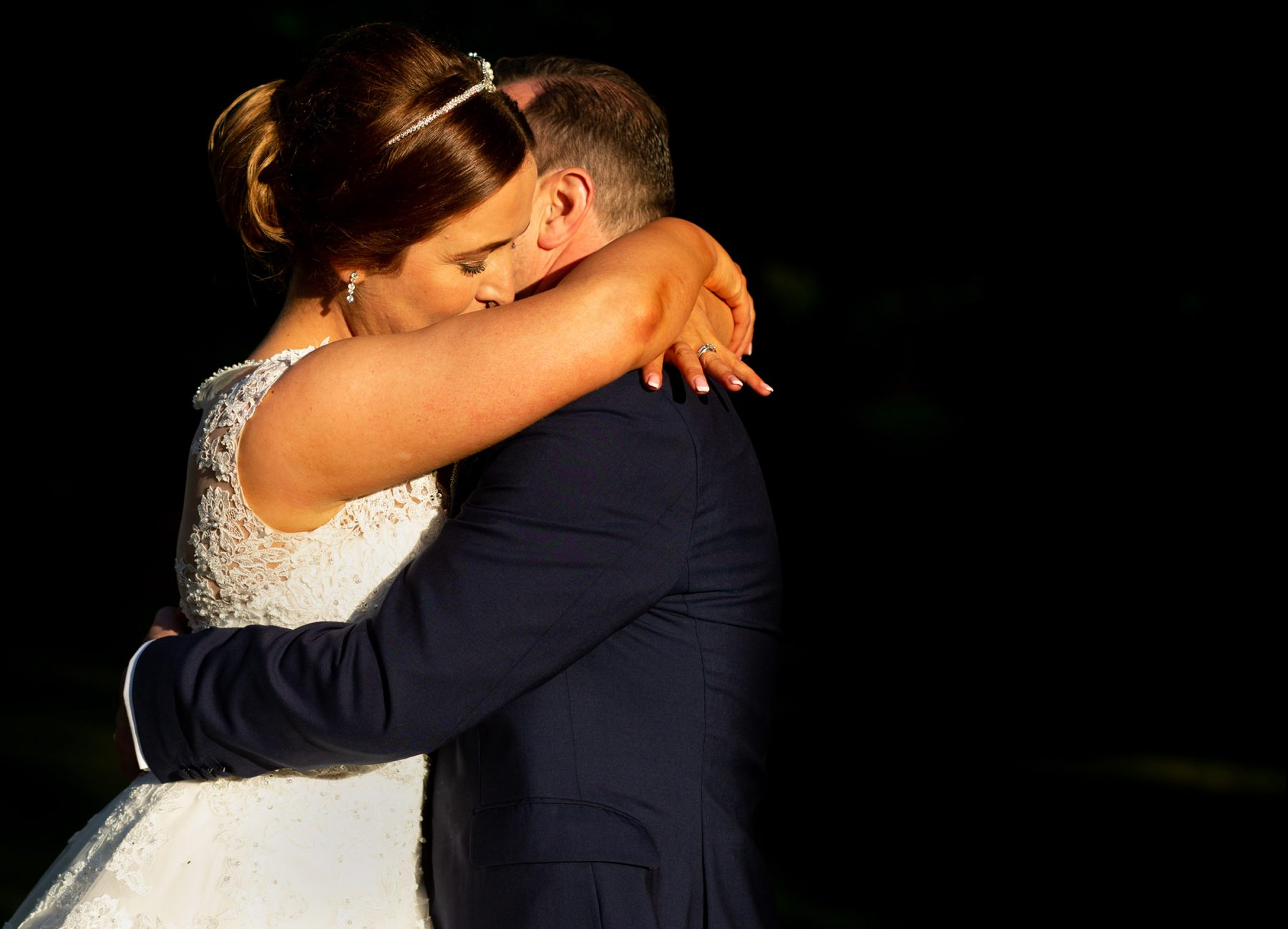 The bride hugs her groom in evening sunlight after thier wedding ceremony
