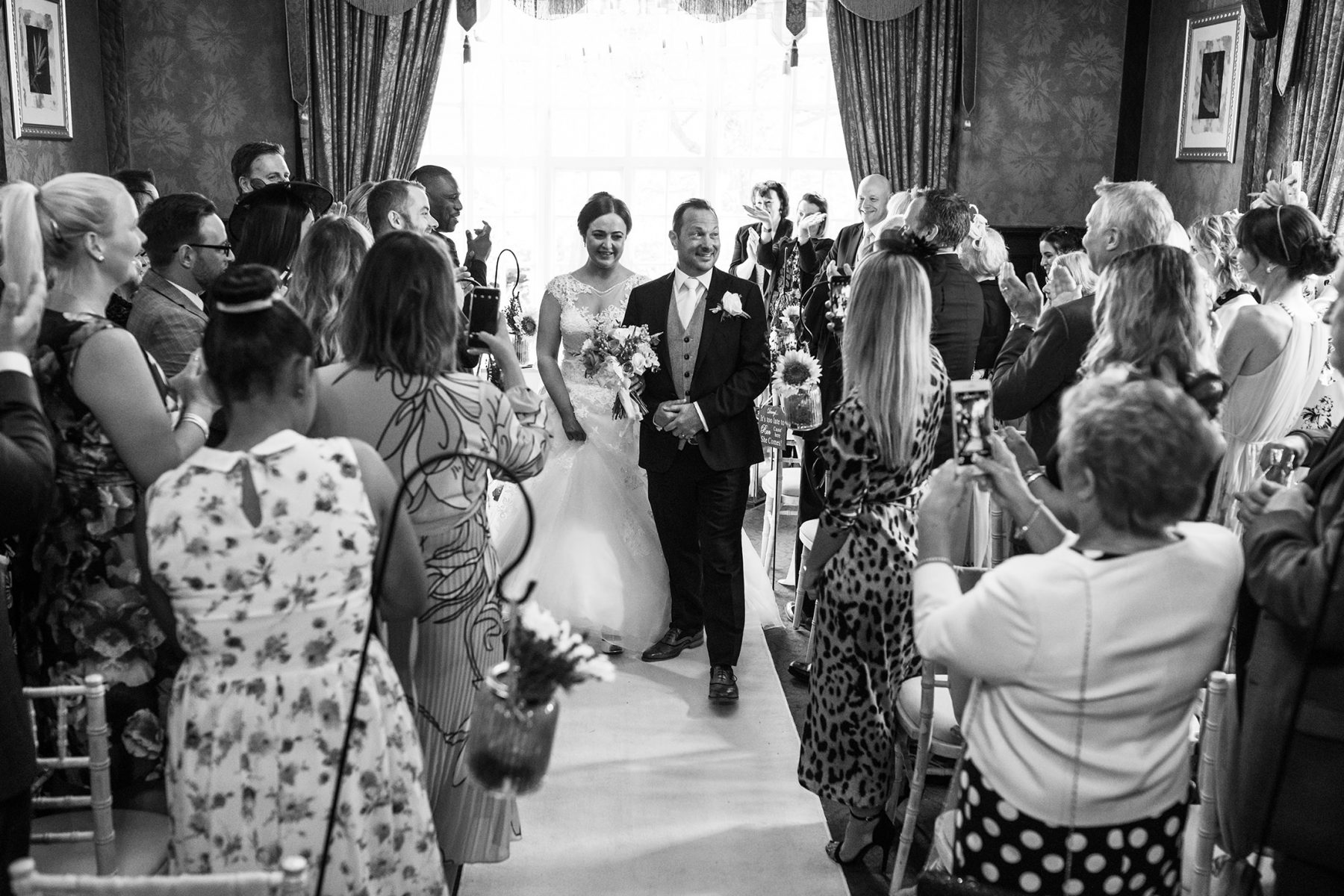 The bride and groom make their way back down the aisle after their wedding at Mere Court Hotel, a historic Knutsford Wedding Venues