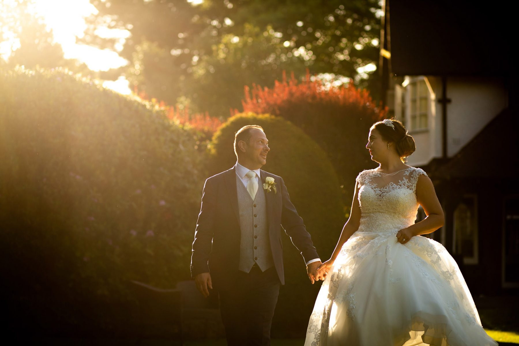 The bride and groom laugh in evening sunlight