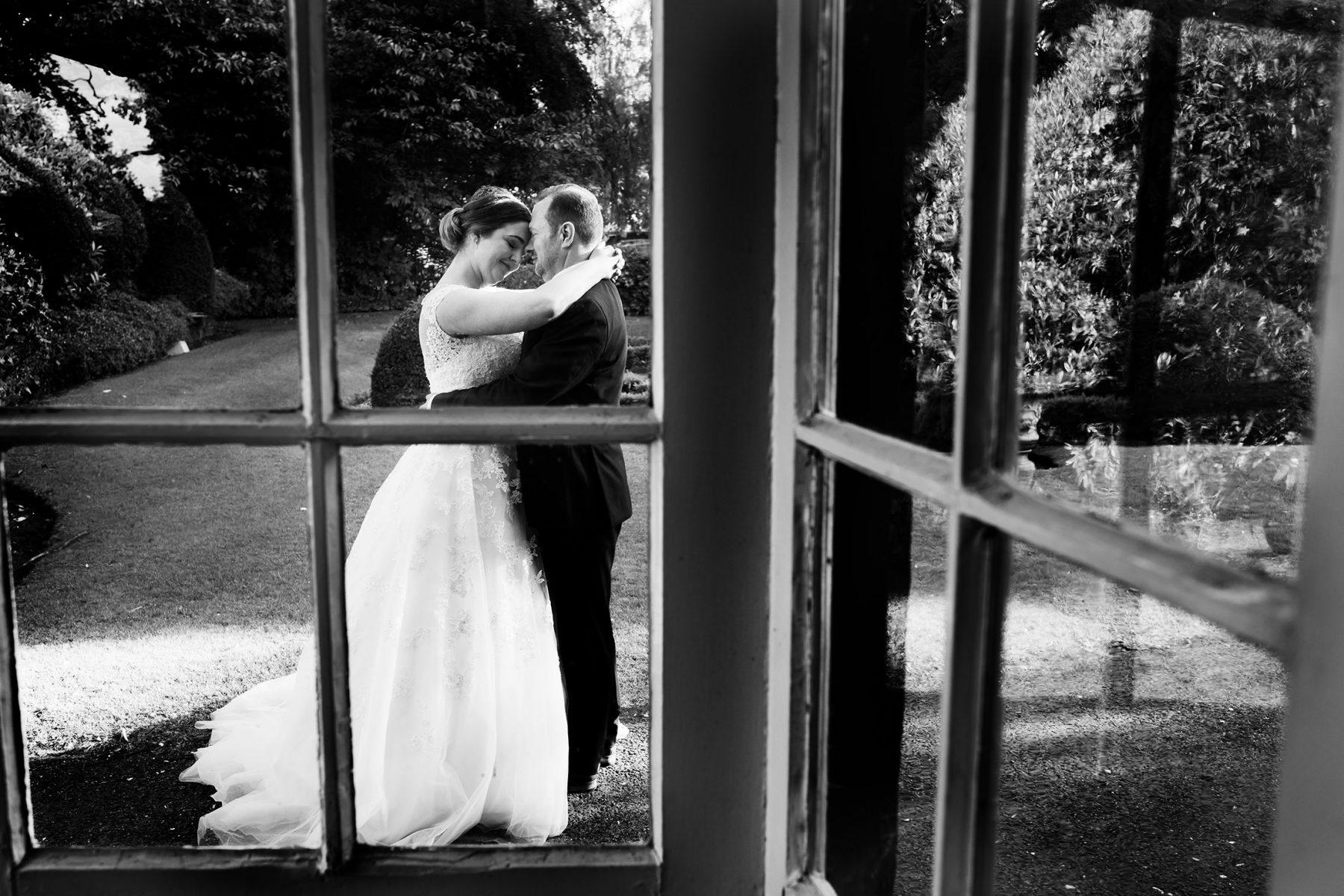 Newleyweds seen hugging though a window