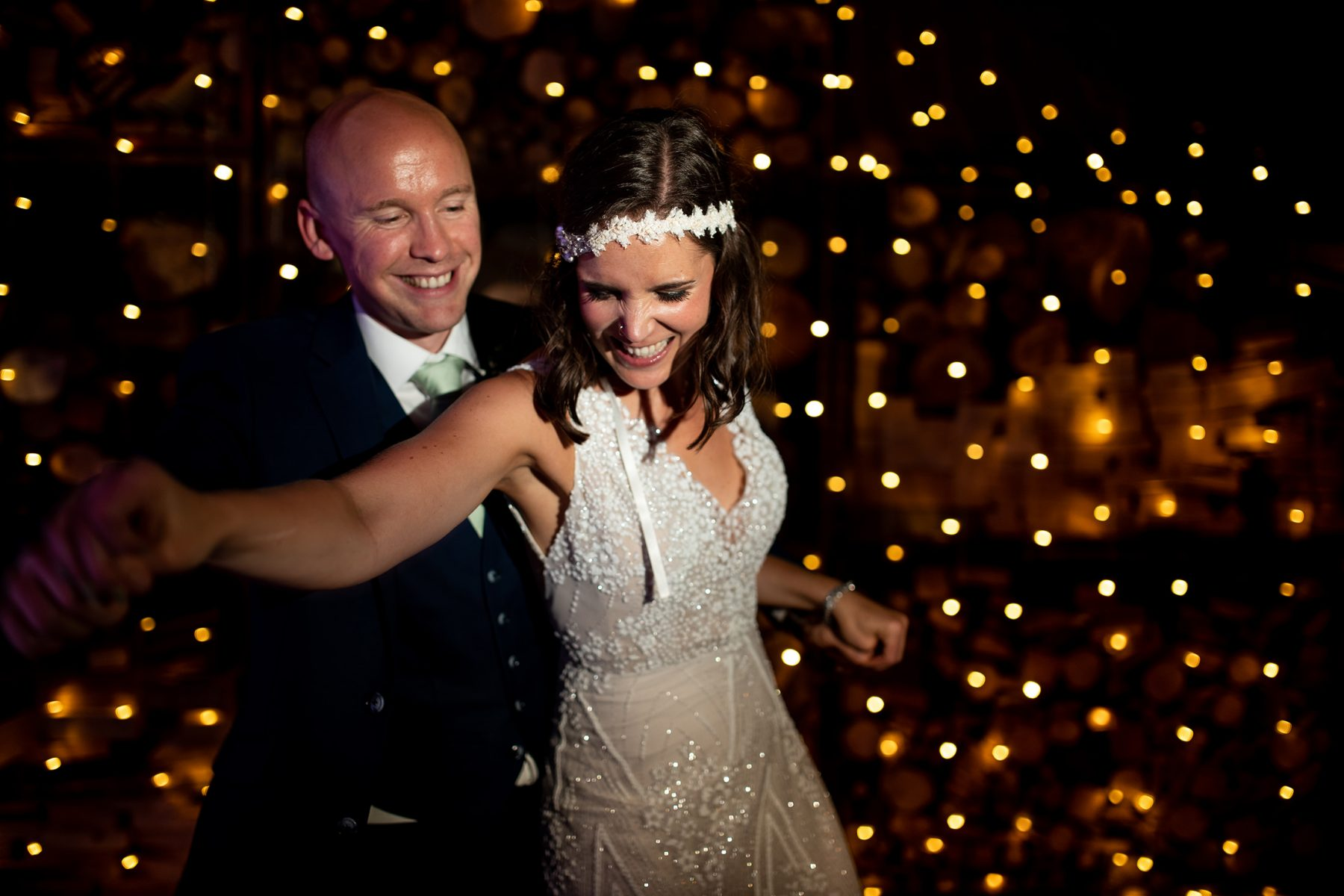 A relaxed wedding photograph showing a relaxed bride and groom as they dance after their wedding