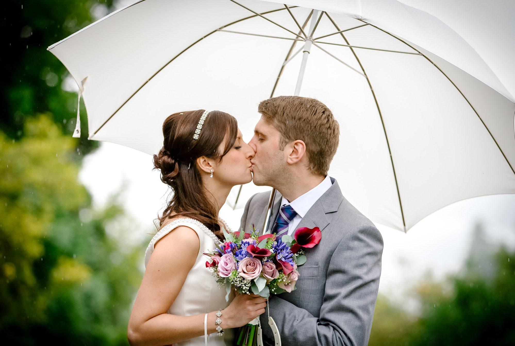 Bride and groom beneath an umbrella - Candid outdoor wedding photography